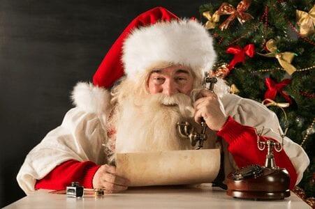 Weihnachtsmann mit altem Telefonhörer in der Hand, der eine Schriftrolle liest und lacht